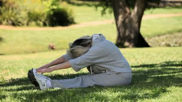 Anciana haciendo caliente para arriba en la hierba — Vídeo de stock