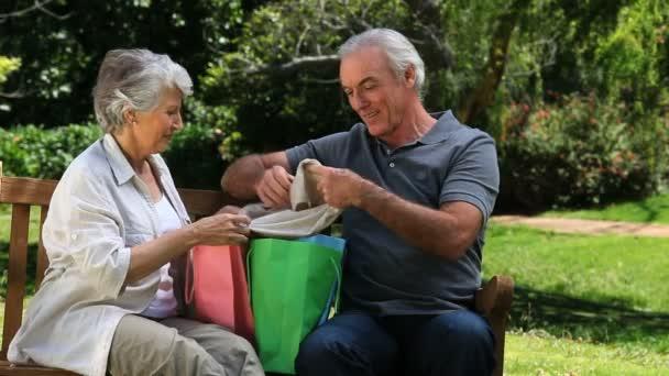 Couple de personnes âgées à la recherche à l'achat sur un banc — Vidéo