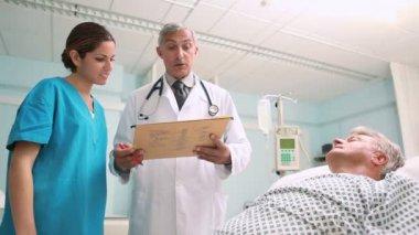 Arts en een verpleegster kijkend naar medische grafiek in een ziekenhuis — Stockvideo