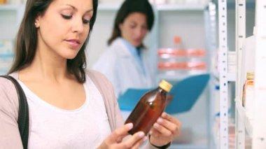Customer in a pharmacy holding a bottle of drug — Stock Video