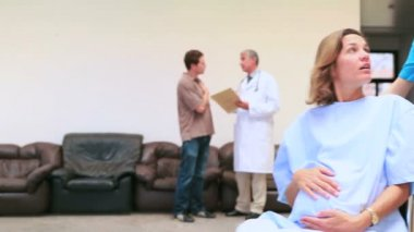 Nurse supervising pregnant woman while doctor speaking with man — Stock Video
