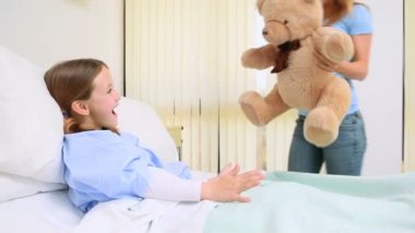 Happy woman giving a teddy bear to a girl in a bed — Stock Video
