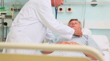мужской доктор auscultating мужчина пациента в кровати уорд — Стоковое видео