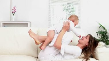 Woman having a baby on her legs and plays with him — Vídeo de Stock