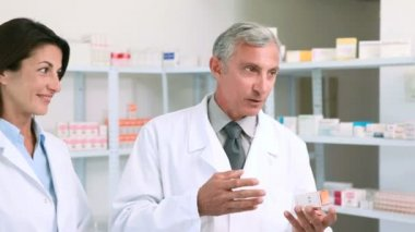 Pharmacist holding a box of pills while talking to a customer — Stock Video