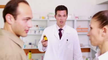 Smiling pharmacist pointing at a flask of pills to a man and a woman — Stock Video