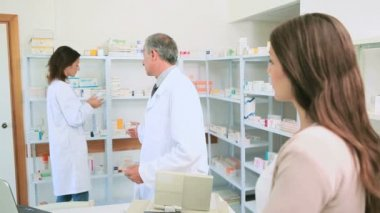 Smiling pharmacist talking to a colleague in front of a female client — Stock Video