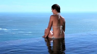 Woman sitting on the edge of swimming pool — Stock Video