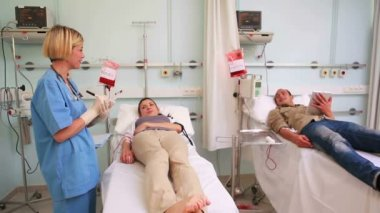 Two transfused patients lying on a medical bed — Stock Video