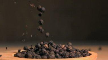 Peppercorns spread in super slow motion in a wooden spoon — Stock Video