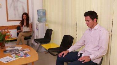 Mannen skakar hand läkare i ett väntrum — Stockvideo