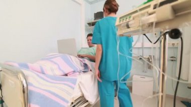 Joyful patient using a laptop while lying on a bed — Stock Video