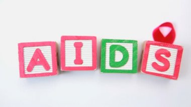 Aids spelled out in blocks with red ribbon — Stock Video