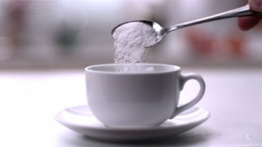 Pouring powdered sugar from teaspoon into a white cup — Stock Video