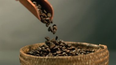 Coffee beans pouring from wooden scooper to basket — Stock Video