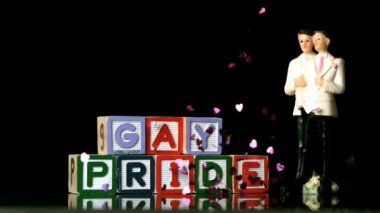 Confetti falling on blocks spelling gay pride with gay cake topper — Stock Video