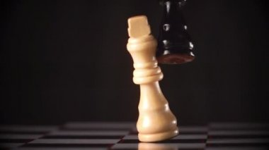 Black king knocking over white king — Stock Video #22754867