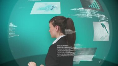 Businesswoman using interactive touchscreen displaying business imagery