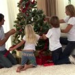 Montage of a family decorating a christmas tree — Stock Video #23037776