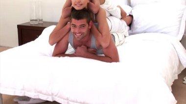 Adorable famille joue ensemble sur le lit — Vidéo