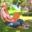 Young woman reading a book with her daughter — Stock Video