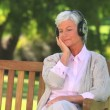 Mature woman listening to music outside — Stock Video