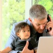 Man talking on phone while his baby is fidgeting on his lap — Stock Video