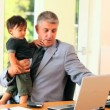 Stock Video: Mdoing office work while holding baby