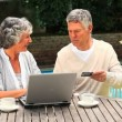 Retired couple using a credit card to buy online — Stock Video #23496771