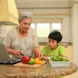 Woman cooking with her grandson — Stock Video #23496799