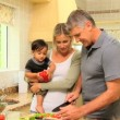 Cute little boy eating a sweet red peper while his father is cooking vegetables — Stock Video #23496805