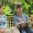 Young couple reading a newspaper outdoors — Stock Video