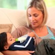 Mother bottle-feeding her baby on sofa — Stock Video