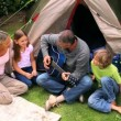 Father playing guitar in front of his family — Stock Video