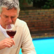 Mature man enjoying a glass of red wine — Stock Video #23498927