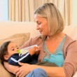 Young mother bottle-feeding baby on sofa — Stock Video #23498987