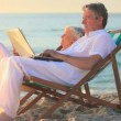 Man using a laptop on a beach while his wife sleeps — Stock Video