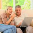 Couple enjoying pictures on laptop on sofa — Stock Video