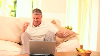 Middle-aged man overjoyed by what he sees on his laptop — Stock Video