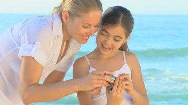 Mother and daughter taking photos on a beach — Stock Video