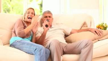 Couple on sofa enjoying an exciting TV programme — Stock Video