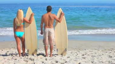 Couple looking at the sea holding their surfboards — Stock Video
