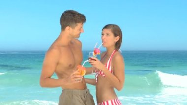 Sweet couple sharing cocktails on a beach — Stock Video