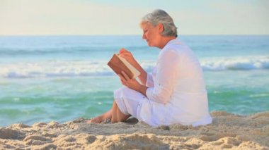 Mature woman reading reading on a beach — Stock Video