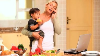 Woman in kitchen coping with baby and laptop and phone — Stock Video