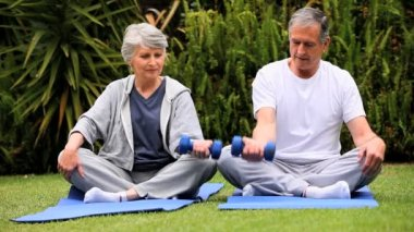 Senior couple doing dumbell exercises on gym mats — Stock Video