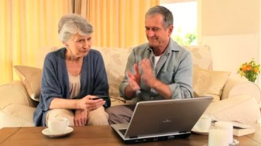 Retired couple happy at having used their laptop successfully — Stock Video