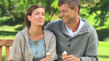 Young couple eating icecream outdoors — Stock Video