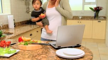 Young mother in kitchen coping with laptop phone and baby — Stock Video