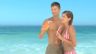 Couple drinking cocktails on a beach — Stock Video